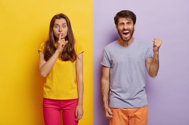 Horizontale aufnahme von junger frau und mann stehen in freizeitkleidung zusammen, drücken unterschiedliche gefühle und emotionen aus frau zeigt stille geste mit überraschtem ausdruck empörter kerl hebt faust vor wut