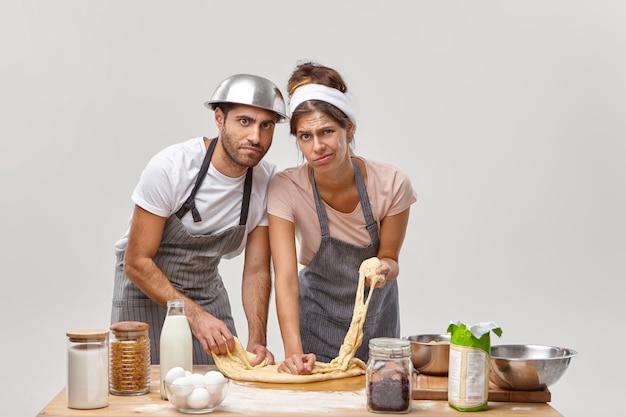 Horizontale aufnahme von müder hausfrau und ehemann bereiten teig mit mehl zum backen von brot vor, probieren neues rezept, müde vom kochprozess, verbringen viele stunden in der küche. vorbereitung für die herstellung von frischem gebäck