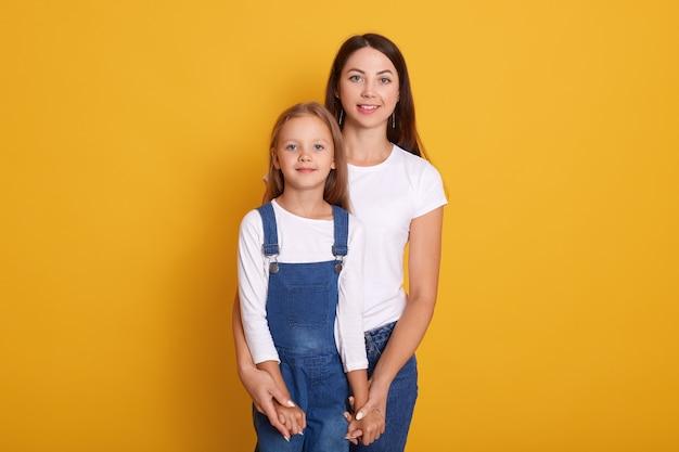 Horizontale aufnahme von mutter mit tochter, glücklich zusammen verbringen, weibliche kleider weißes t-shirt, niedliches kleines mädchen, das overalls trägt