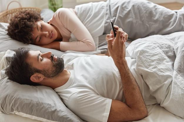 Horizontale aufnahme von unrasierten süchtigen kerl verwendet smartphone-anwendung, hält handy