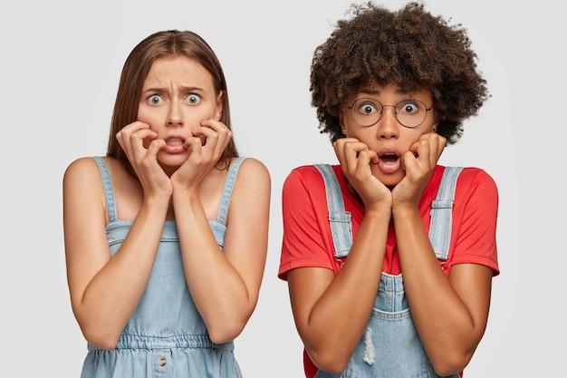 Horizontale aufnahme von verblüfften frauen gemischter rassen starren