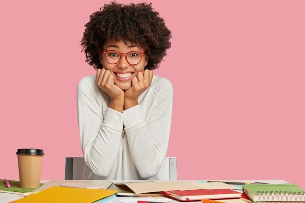 Horizontale aufnahme von ziemlich glücklichen schwarzen jungen weiblichen designer grinst, hat zahniges lächeln