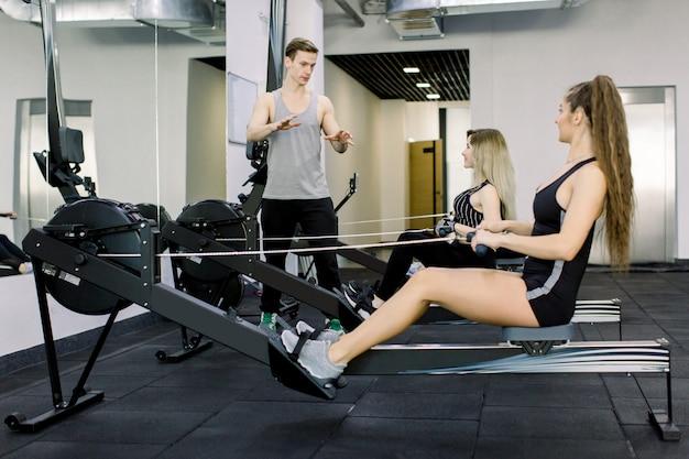 Horizontale aufnahme von zwei jungen sportlerinnen, die im fitnessstudio auf sitzender reihenkabelmaschine trainieren. hübscher trainer, der berät, wie man übungen macht