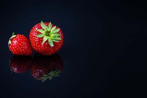 Horizontale aufnahme von zwei roten kroatischen erdbeeren auf schwarzer reflektierender oberfläche - raum für ihren text