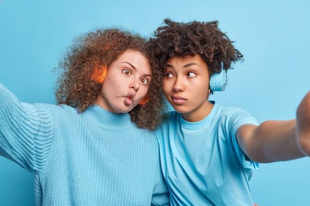 Horizontale aufnahmen von lustigen verschiedenen frauen machen lustige gesichtsposen für selfie-musik hören über kopfhörer stehen nebeneinander an der blauen wand. die besten mixed-race-freunde haben indoor-spaß.
