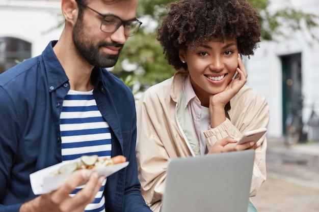 Horizontale außenaufnahme von familienpaaren gemischter rassen ruhen im fremden land, essen köstlichen hot dog.