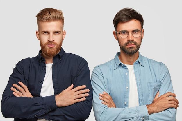 Horizontale einstellung von ernsthaften, selbstbewussten männern, die etwas aufmerksam zuhören, genau stehen und die hände über der brust drücken