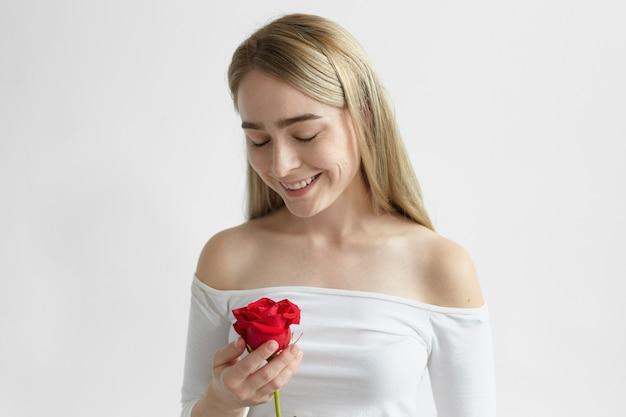 Horizontale entzückende glückliche junge europäische frau mit losen blonden haaren, die breit lächeln, eine schöne rote rose vom fremden halten. menschen, romantik, liebe und zuneigung konzept