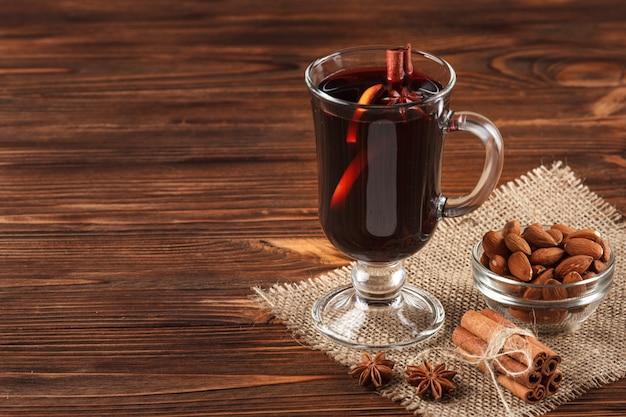Horizontale glühweinfahne des winters. gläser mit heißem rotwein und gewürzen auf hölzernem hintergrund.