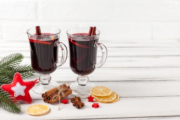 Horizontale glühweinfahne des winters. gläser mit heißem rotwein und gewürzen, baum, filzdekorationen