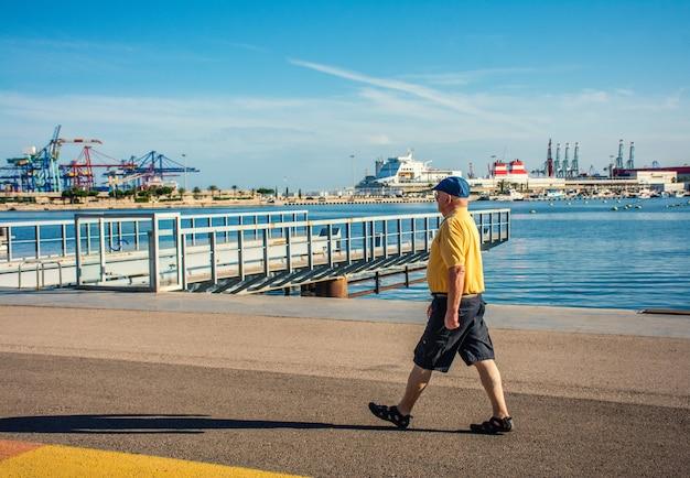 Horizontale helle ansicht eines älteren mannes, der an einem sonnigen tag an einem stadtufer spazieren geht