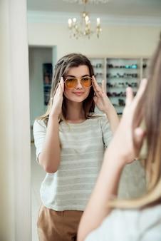 Horizontale innenaufnahme der trendigen modernen frau im lässigen outfit, das nahe spiegel im optikergeschäft steht