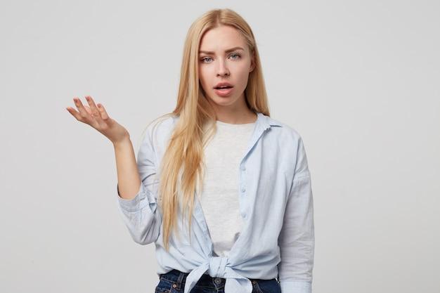 Horizontale innenaufnahme der wütenden jungen blonden frau, die mit erhabener handfläche steht und genervt und mürrisch aussieht