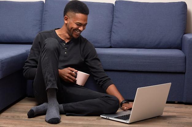 Horizontale innenaufnahme des dunkelhäutigen mannes, der auf boden nahe blauem sofa aufwirft, sieht lustiges video auf laptop-computer an