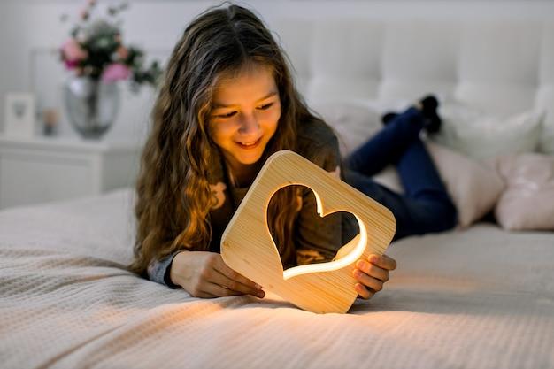 Horizontale innenaufnahme des schönen schulmädchens des kindes, das zu hause auf dem bett liegt und spaß mit der stilvollen handgemachten hölzernen nachtlampe mit herzbild hat.