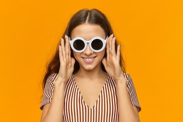 Horizontale isolierte aufnahme der modischen glamourösen jungen europäischen frau