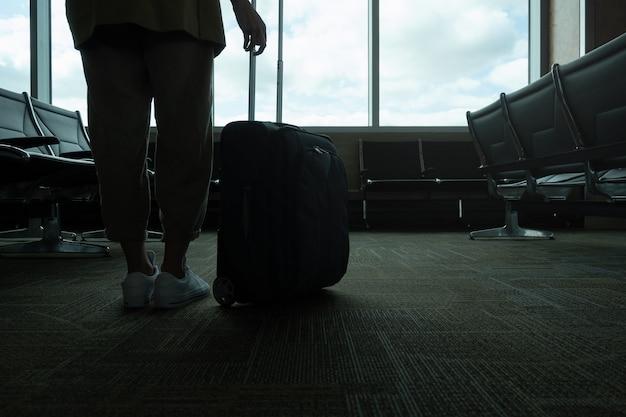 Horizontale nahaufnahme einer nicht erkennbaren frau mit hintergrundbeleuchtung mit koffer am flughafen, mit kopierraum.
