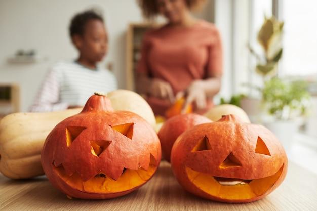 Horizontale nahaufnahme von kürbissen, die mutter und ihr sohn für die halloween-party zu hause geschnitzt haben