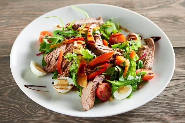 Horizontale nahaufnahmeaufnahme des köstlichen frisch gemachten salats mit fleischeiern und -gemüse auf dem holztisch, der essen, mittagessen, abendessen, gourmet-mix, gehackte, gesunde lebensmittel isst.