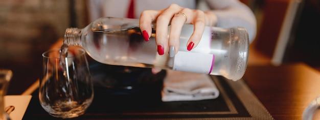 Horizontale nahaufnahmetabelleneinstellung im restaurant. nicht erkennbare frauenhand, die eine flasche hält, die frisches wasser in das glas gießt.