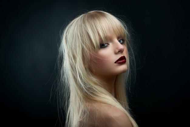 Horizontale seitenansicht des blonden mädchens roten lippenstift tragend.
