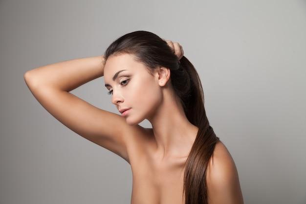 Horizontale studioaufnahme der jungen frau, die ihr langes glattes haar hält.