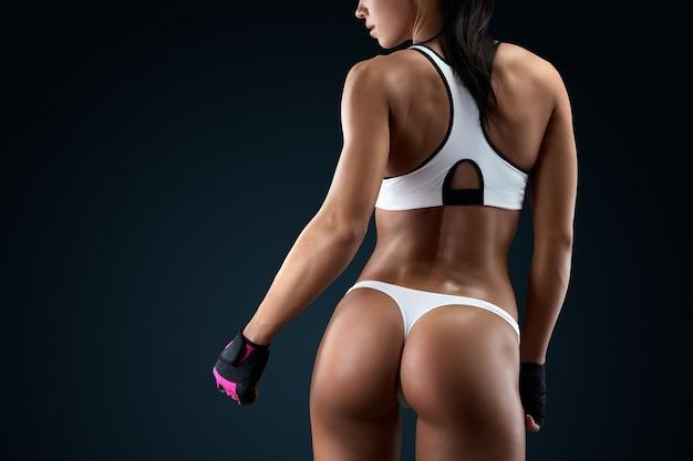 Horizontale studioaufnahme mit kopienraum auf schwarzem hintergrund. verschwitzte frau, die eine pause in einem fitnessstudio macht und ihren gut trainierten körper zeigt. rückansicht der fitnessfrau mit muskulösem körper.