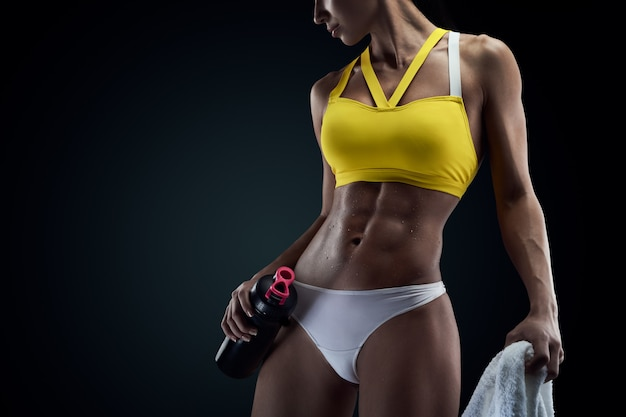 Horizontale studioaufnahme von perfekten bauchmuskeln einer sportlerin auf schwarzem hintergrund mit exemplar