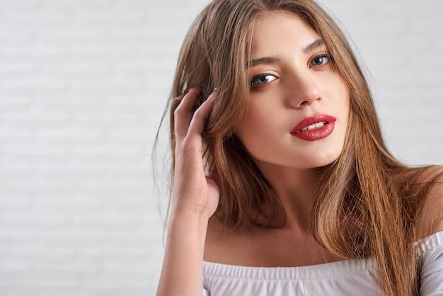 Horizontaler abschluss herauf schuss des schönen kaukasischen modells mit rotem lippenstift und auge bilden die aufstellung vor unscharfem