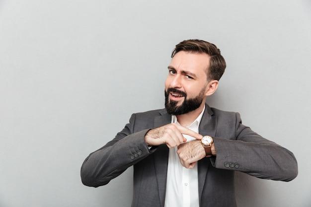 Horizontaler bärtiger mann, der auf seine armbanduhr, aufstellung lokalisiert über grau zeigt