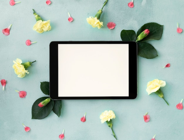 Horizontaler digitaler tablettenkopienraum umgeben durch blumen
