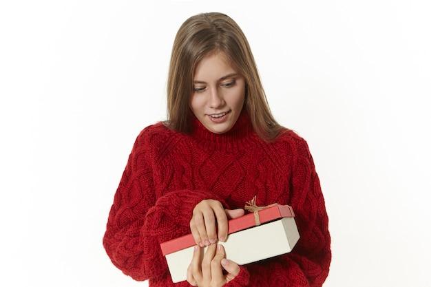 Horizontaler schuss der attraktiven stilvollen jungen dame, die kastanienbraun gestrickten pullover hält box hält, es öffnet, aufgeregt ist, geschenk an ihrem geburtstag empfangend. hübsches mädchen, das mit papierkasten aufwirft