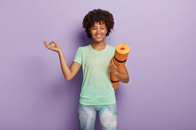 Horizontaler schuss der erfreuten dunkelhäutigen gesunden frau meditiert, hat yogaübungen, trägt fitnessmatte