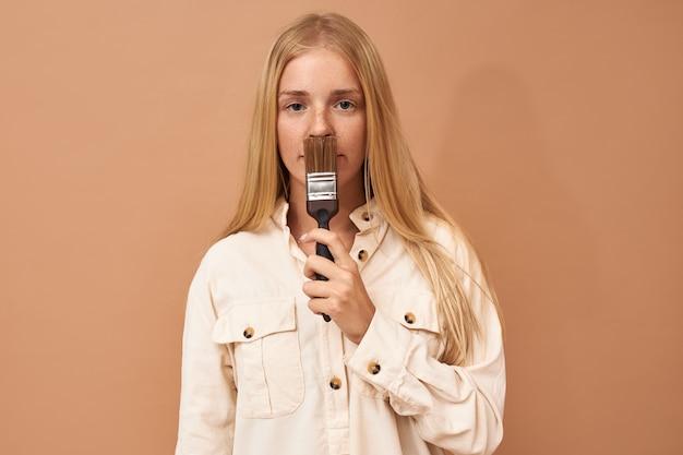 Horizontaler schuss der ernsten jungen frau mit dem langen blonden haar, das mit bürste lokalisiert aufwirft
