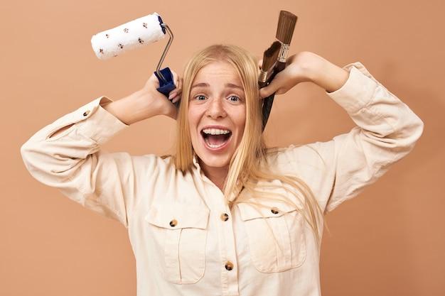 Horizontaler schuss der glücklichen emotionalen jungen blonden frau im stilvollen hemd, das spezielle werkzeuge hält, während reparatur in ihrer wohnung, aufgeregt über renovierung