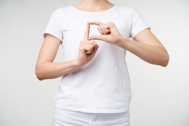 Horizontaler schuss der hände der jungen frau, die angehoben werden, während gedanken ohne wörter ausgedrückt werden, wort auf gebärdensprache zeigend, lokalisiert über weißem hintergrund