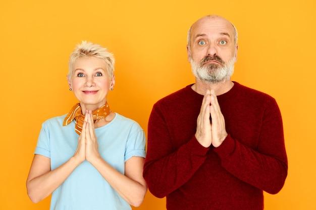 Horizontaler schuss der ruhigen friedlichen energetischen frau mittleren alters, die ehemann lehrt, wie man yoga praktiziert, beide hände zusammengedrückt halten, namaste geste tun. menschen, altern und wohlbefinden konzept