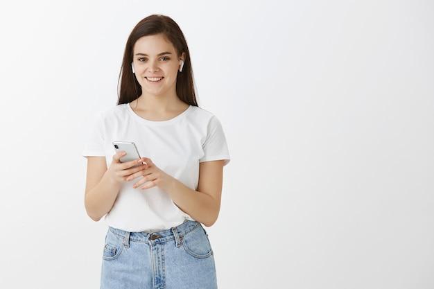 Horizontaler schuss der sorglosen jungen frau, die mit ihrem telefon und den ohrhörern gegen weiße wand aufwirft