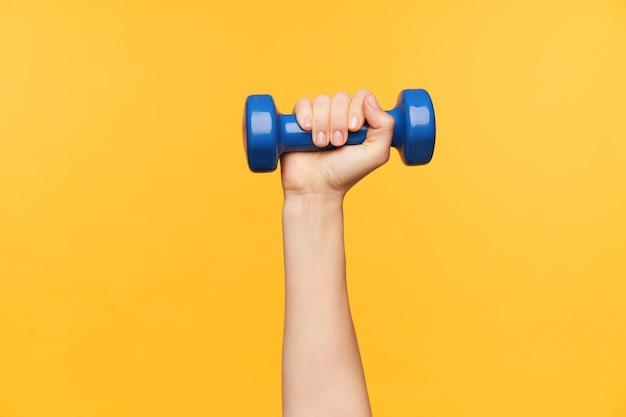 Horizontaler schuss der weiblichen hand, die angehoben wird, während man körperliche übungen mit gewichtungsmittel macht, lokalisiert über gelbem hintergrund. gewichtsverlust und fitness-konzept