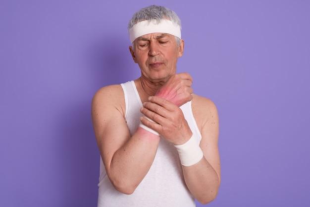 Horizontaler schuss des älteren mannes kleidet weißes ärmelloses t-shirt, verletzt sein handgelenk während des sporttrainings