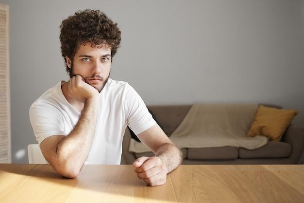 Horizontaler schuss des attraktiven ernsten jungen mannes mit stoppeln, die gelangweilten gesichtsausdruck haben, das wochenende allein zu hause verbringen, am hölzernen schreibtisch gegen weiße wand sitzen,