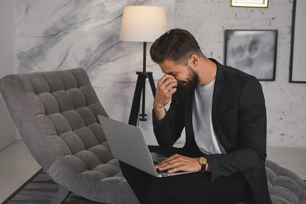 Horizontaler schuss des attraktiven fröhlichen jungen geschäftsmannes mit dem dicken bart und der stilvollen frisur, die gesicht bedeckt, während über witz oder meme lachen, während der arbeitspause soziale netzwerke auf laptop surfen