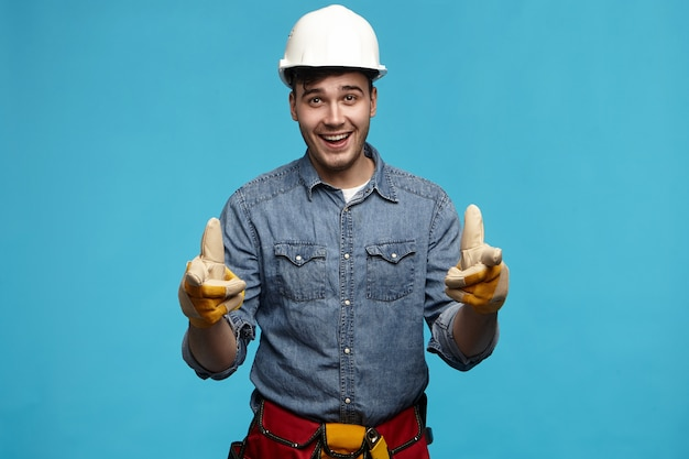 Horizontaler schuss des attraktiven jungen unrasierten männlichen baumeisters, der schutzhelm trägt