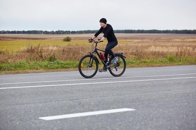 Horizontaler schuss des bikers, der schwarzen bahnanzug trägt, der auf asphaltstraße mit markierungen reitet, sportlicher mann, der straßenradfahren genießt