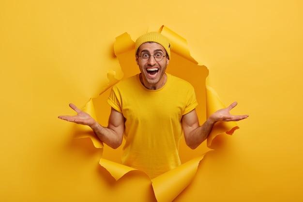 Horizontaler schuss des freundlich aussehenden glücklichen kaukasischen mannes breitet hände seitwärts aus, präsentiert etwas cooles, gekleidet in freizeitkleidung, posiert allein im papierloch