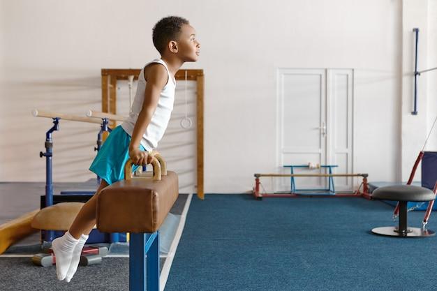Horizontaler schuss des geschickten atheltischen afroamerikanischen jungen in der sportbekleidung, die auf pauschenpferd montiert Kostenlose Fotos