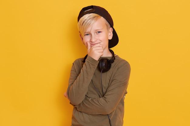 Horizontaler schuss des glücklichen blonden kleinen jungen stellt lokalisiert über gelb dar, tragend schwarze rückwärtige kappe, grünes hemd