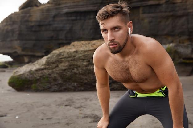 Horizontaler schuss des gutaussehenden entschlossenen sportlichen mannes lehnt sich an die knie