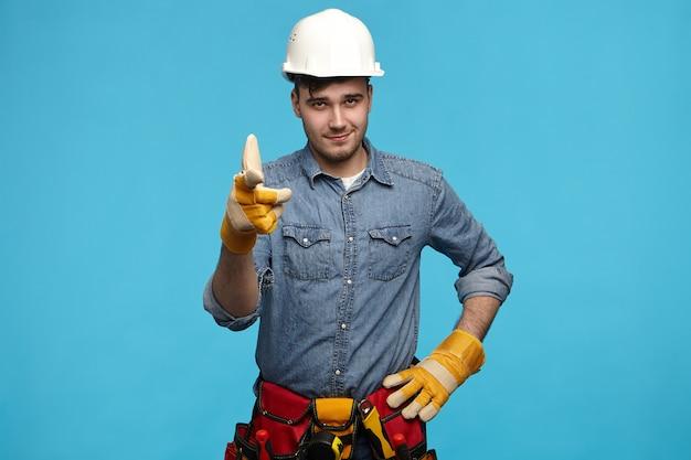 Horizontaler schuss des hübschen jungen wartungsdienstarbeiters, der weißen helm trägt