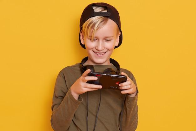 Horizontaler schuss des kleinen jungen, der schwarze kappe und grünen kapuzenpulli trägt, posiert mit handy in den händen, modisches kind, das online-spiele spielt.